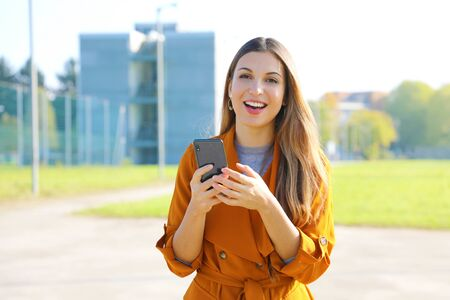 Happy cheerful casual woman walking in the street using a smartphone and looking at camera.