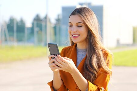 Young pretty woman texting outdoors. Beautiful young stylish woman in orange jacket with phone on street.