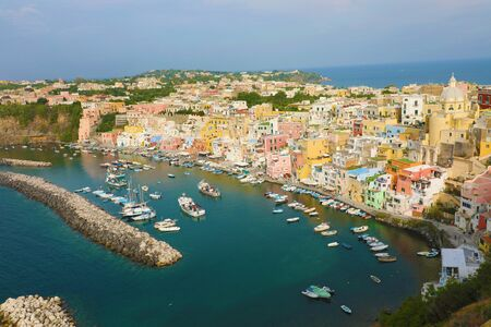 Panoramic view of beautiful Procida in sunny summer day. Colorful houses, cafes and restaurants, fishing boats and yachts in Marina Corricella, Procida Island, Italy.