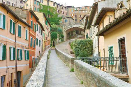 Perugia, Italy. Old medieval aqueduct and colorful buildings. Фото со стока