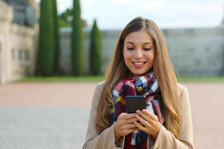 Young business woman typing message by phone walking on the city square wearing coat and scarf in winter.