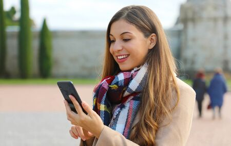 Happy cheerful young woman typing with finger on smart phone on city square wearing coat and scarf in winter.