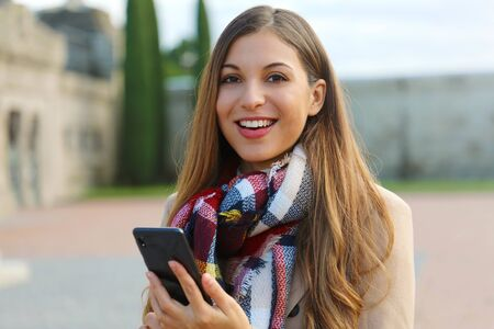 Happy cheerful young woman looks at you holding mobile phone on city square wearing coat and scarf in winter.