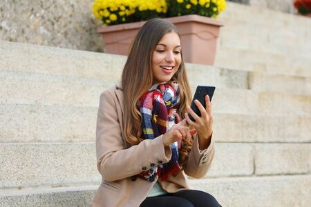 Pretty cheerful young woman typing with finger on smart phone sitting on stairs wearing coat and scarf in winter time.