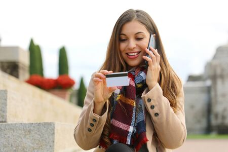 Smiling woman sitting outdoors looking at number on credit card and confirm purchase via telephone call to customer service. Positive girl making payment via smartphone conversation outside.