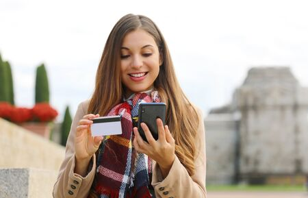 Young shopper woman holding credit card buying online with smart phone sitting outdoor. Фото со стока