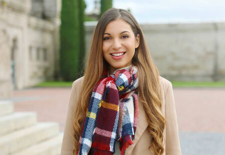 Portrait of smiling young woman wearing coat and scarf outdoor in winter. Фото со стока