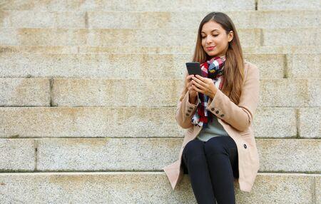 Beautiful stylish woman sitting on street stairs using mobile phone on winter day.