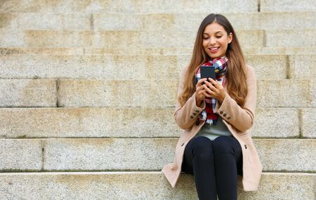 Smiling beautiful young woman sitting on stairs using mobile phone on winter day.