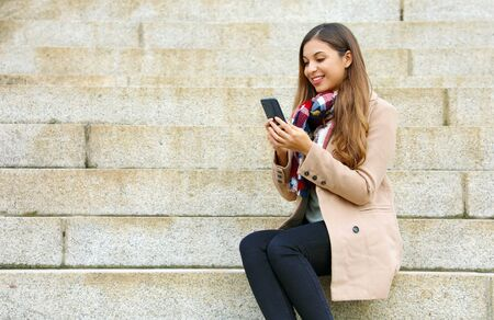 Happy smiling young business woman sitting on stairs reading or sending message with app on smart phone on winter day.