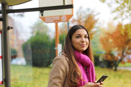 People and public transport. Beautiful young woman holding mobile phone waiting the bus on bus stop.