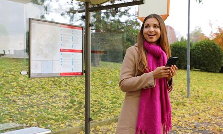 People and public transport. Smiling beautiful young woman holding mobile phone watch the bus arrive on bus stop.