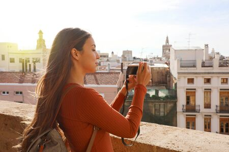 Side view of traveler girl taking picture from terrace of Valencia cityscape, Spain.
