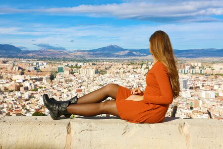 Beautiful young woman sitting on wall looking at stunning panoramic cityscape of Alicante in Spain, Europe.
