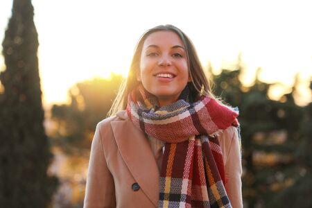 Femme d'hiver souriante à l'extérieur au coucher du soleil