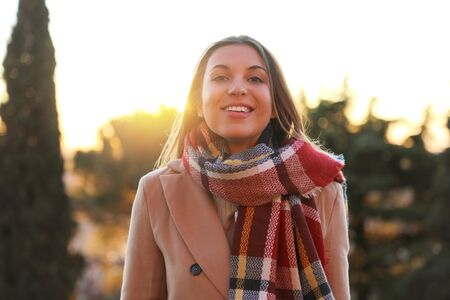 Smiling winter woman outdoors at sunset