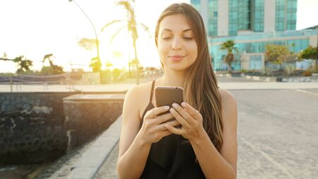 Smiling young woman sending message with smart phone at sunset with seaside town on the background. Positive trendy girl blogging in social network using mobile phone with internet.