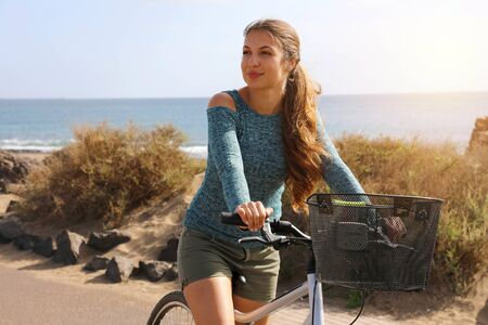 Female cyclist rides along the promenade on a summer day. Young woman riding her bicycle on bike lane with sea on background.