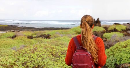 Hiking in spring time. Back view of girl exploring the northern of the island of Lanzarote, Canary Islands. Panoramic banner view of young backpacker woman discovering wild region of Lanzarote. Stock Photo
