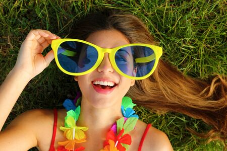 Close up of girl wake up lying on grass after Carnival party. Portrait of pretty young woman with big funny sunglasses and carnival garland.