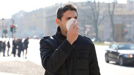 COVID-19 Homme dans la rue de la ville portant un masque protecteur contre la propagation du virus de la maladie : Coronavirus Disease 2019. Gros plan sur un homme avec un masque chirurgical sur le visage contre le SRAS-CoV-2.