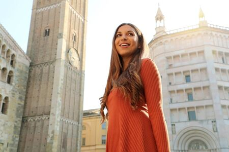 Happy beautiful woman enjoying her vacations in Italy. Smiling traveler girl enjoying her holidays in Parma, Italy.