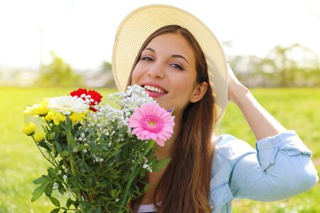 Spring time. Teenager girl holds flower bouquet outdoor. Archivio Fotografico