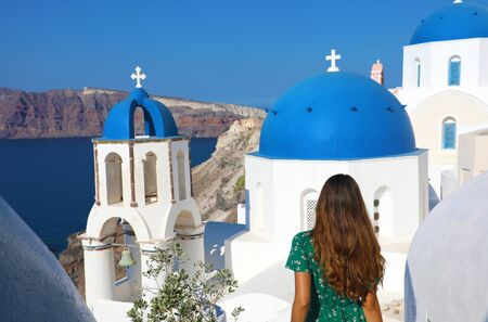Tourism in Greece. Back view of traveler tourist girl visiting the famous white village with blue domes of Oia, Santorini. European travel destination. Standard-Bild