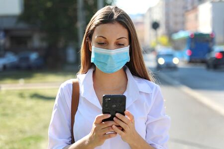 COVID-19 Pandemic Coronavirus Young Woman Wearing Surgical Mask Using Smart Phone App in City Street to Aid Contact Tracing in Response to the 2019-20 Coronavirus Pandemic
