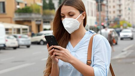 COVID-19 Young Woman Wearing KN95 FFP2 Mask Using Smart Phone Application Software in City Street to Aid Contact Tracing and Self Diagnostic in Response to the Pandemic Coronavirus 2019