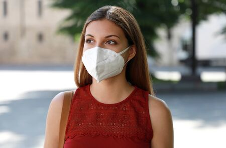COVID-19 Worried girl in city street wearing KN95 FFP2 mask protective for spreading of disease virus SARS-CoV-2. Girl with protective mask on face against Coronavirus Disease 2019. 版權商用圖片