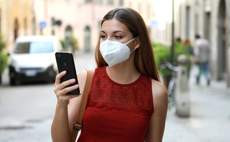 COVID-19 Portrait of Young Woman Wearing KN95 FFP2 Mask Using Smart Phone App in City Street to Aid Contact Tracing and Self Diagnostic in Response to Coronavirus Disease 2019