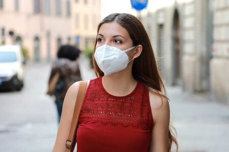 COVID-19 Young woman walking in city street wearing KN95 FFP2 mask protective for spreading of disease virus SARS-CoV-2. Girl with protective mask on face against Coronavirus Disease 2019.