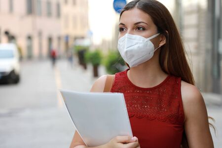 COVID-19 Global Economic Crisis Unemployed Worried Girl with KN95 FFP2 Mask  Looking for Job Walking in City Street Delivering Curriculum Vitae Archivio Fotografico