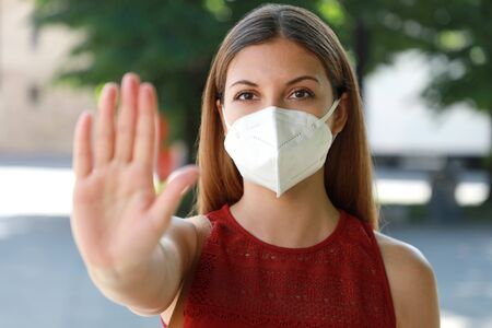 STOP COVID-19 Young Woman Wearing KN95 FFP2 Mask on her Face Showing Gesture STOP Looking at Camera Outdoors. Girl with face mask showing open hand palm at the camera against Coronavirus disease 2019.