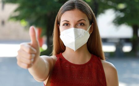 COVID-19 Optimistic girl wearing protective mask KN95 FFP2 avoiding Coronavirus disease 2019 showing thumbs up in city street 免版税图像