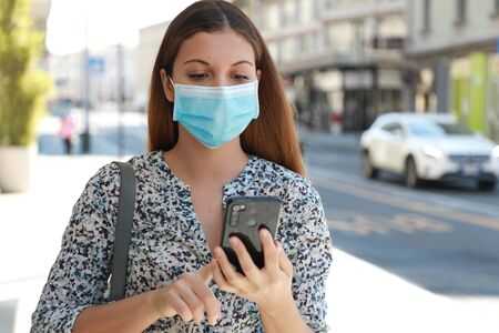 Portrait of young beautiful business woman wearing surgical mask typing on mobile phone in city street
