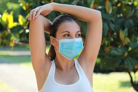 Armpit epilation hair removal sporty woman showing armpits outdoor. Girl stretching in park showing shaved armpits hairless. Happy relaxed woman with surgical mask laser hair removal concept. Banque d'images