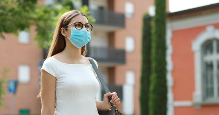 Portrait of young woman walking in city street wearing protective mask