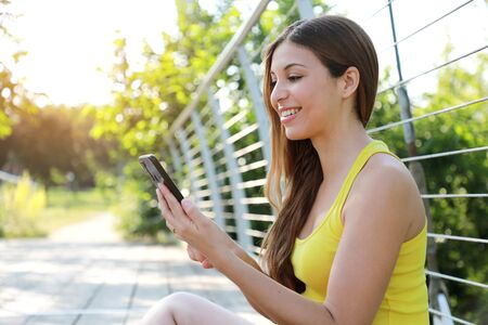 Beautiful sporty girl sitting in the park using smart phone app tracking performance after running workout