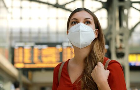 It's time to go back to travel. Close up of traveler girl wearing KN95 FFP2 face mask at train station. Young caucasian woman with timetables information of departures arrivals on behind.