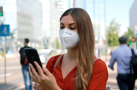 Business woman wearing KN95 FFP2 face mask walking in modern city street holding a smartphone with people on the background