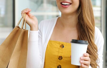 Cropped portrait of young stylish lady with shopping bags holding paper cup of coffee showing brand name