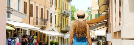 Back view of tourist woman with hat Peschiera del Garda old town in Italy. Panoramic banner view. Archivio Fotografico