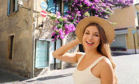 Close up of young tourist woman holding hat visiting Sirmione old flowered town on Lake Garda, Italy