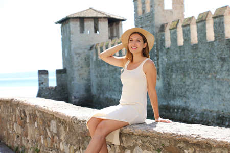 Portrait of fashion model girl sitting on medieval wall of Sirmione Castle on Lake Garda, Italy Archivio Fotografico