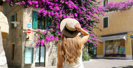 Back view of young tourist woman holding hat visiting Sirmione old flowered town on Lake Garda, Italy
