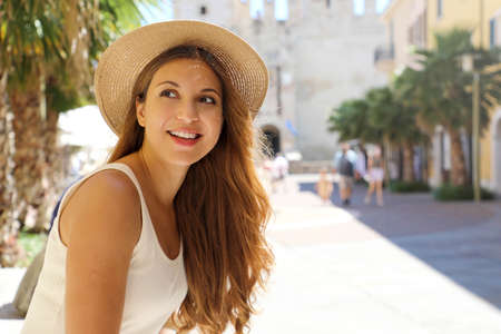 Portrait of young traveler woman visiting Europe. Beautiful tourist girl enjoying her holidays in Sirmione, Italy.