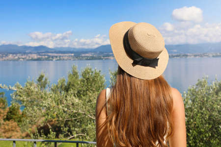 Attractive tourist woman with hat enjoying view of Lake Garda from Sirmione, Italy
