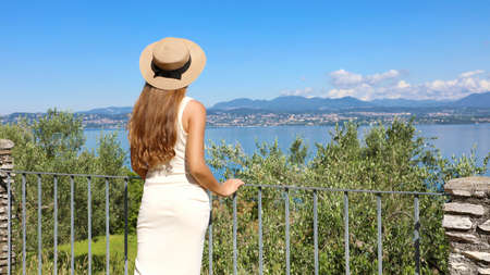 Pretty tourist woman with hat enjoying view of Lake Garda from Sirmione town, Italy